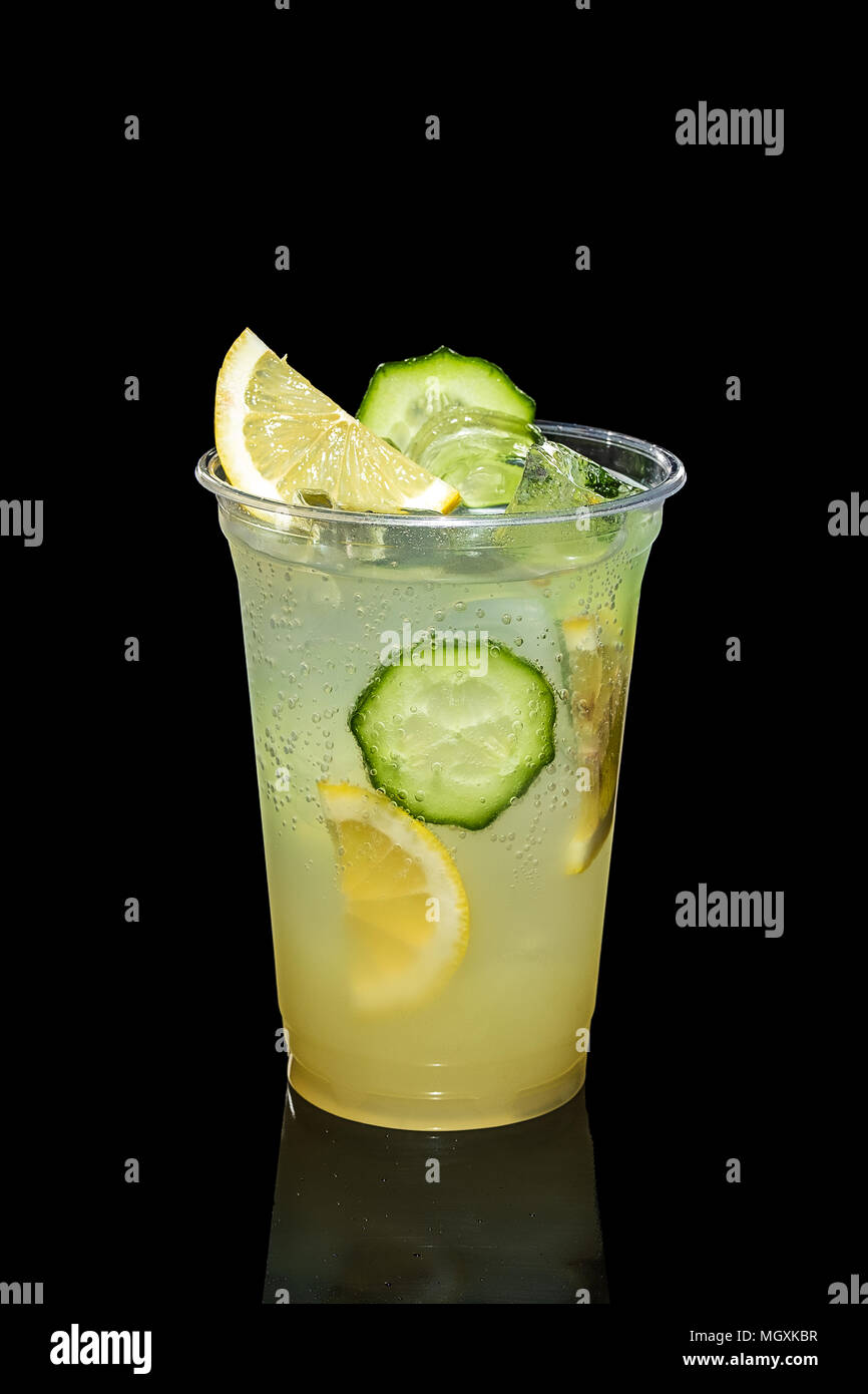 Cold Lemon and cucumber cocktail with a sparkling wine with ice cubes in take away glass isolated on black - Stock Image