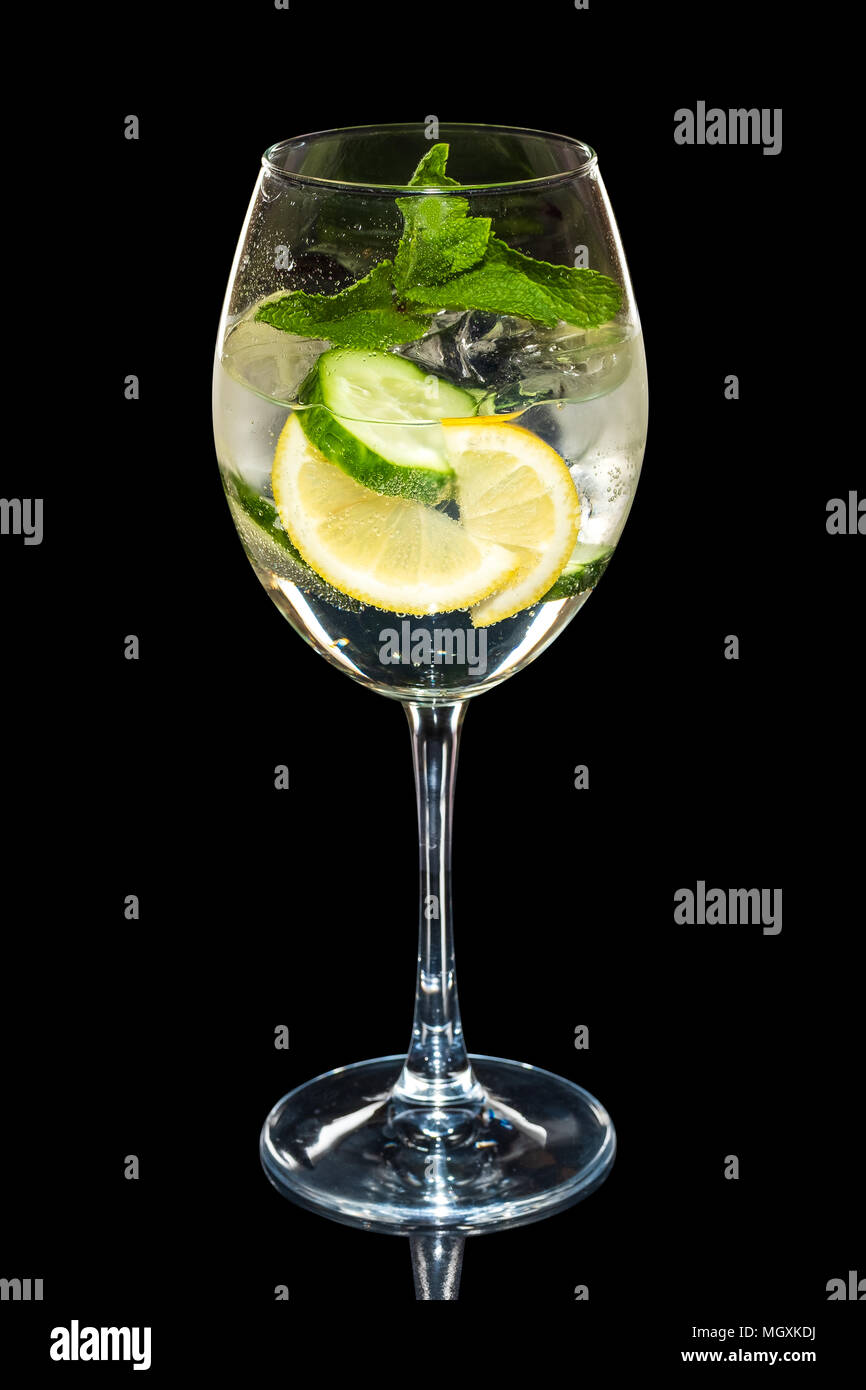 Cold Lemon and cucumber cocktail with a sparkling wine with ice cubes in wine glass isolated on black - Stock Image