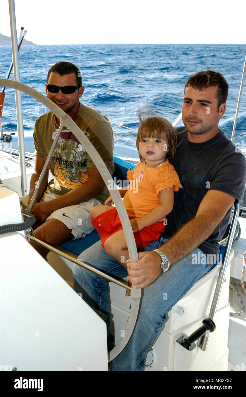 Father and son at the helm of their catamaran, catering for tourist short excursions in Calvi marina on the harbour front at Calvi in Corsica, a Frenc - Stock Image