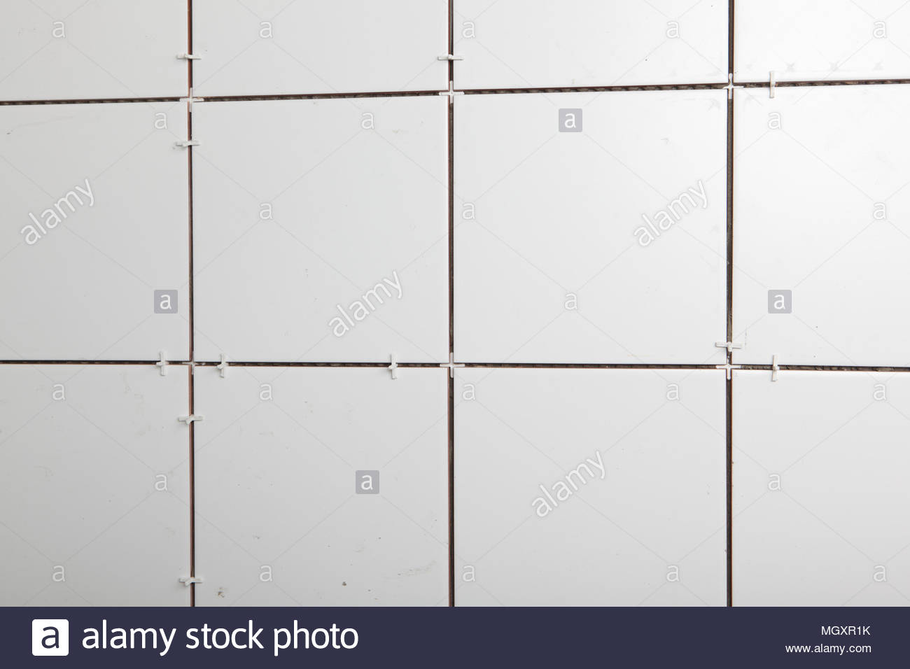 Tiled wall with tile spacers - Stock Image