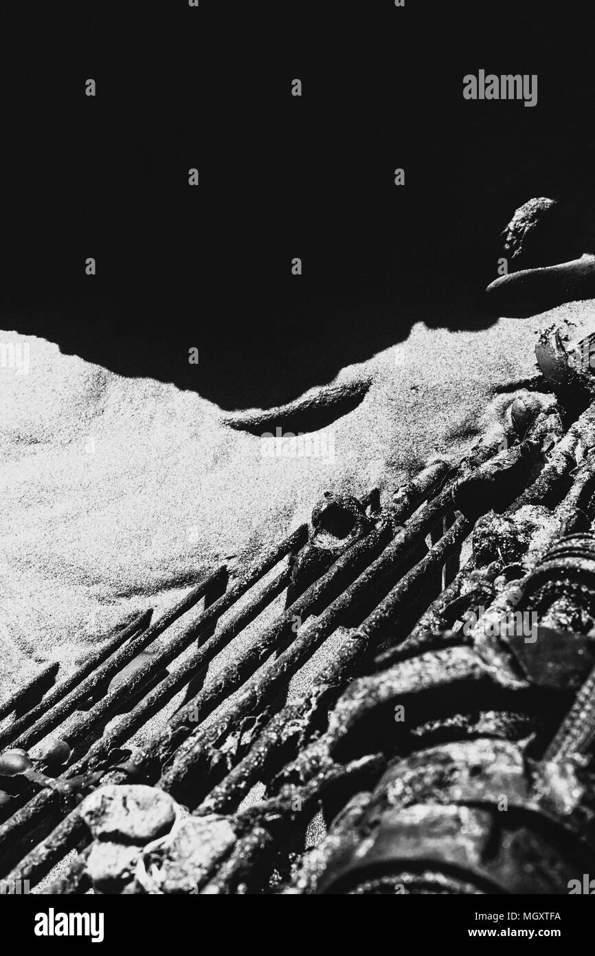 A close up black and white photograph of a lobster pot buried in the