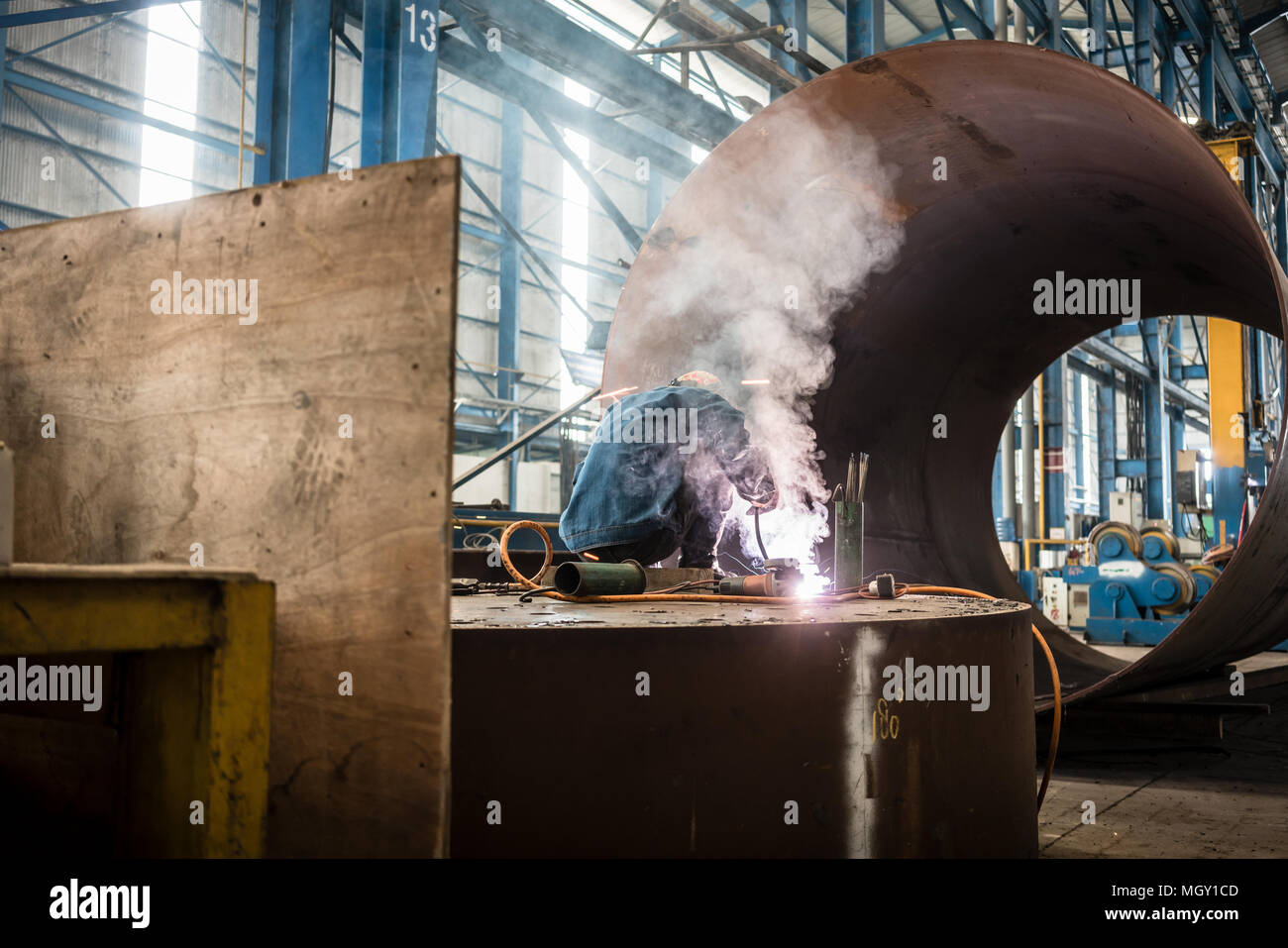 Blue-collar worker welding in the interior of a factory - Stock Image