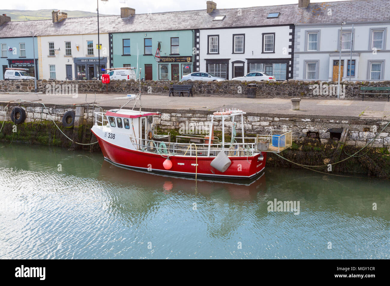 Carnlough, N. Ireland/United Kingdom - June 2, 2015: In the harbor at Carnlough in County Antrim sits a colorful boat on a day. - Stock Image