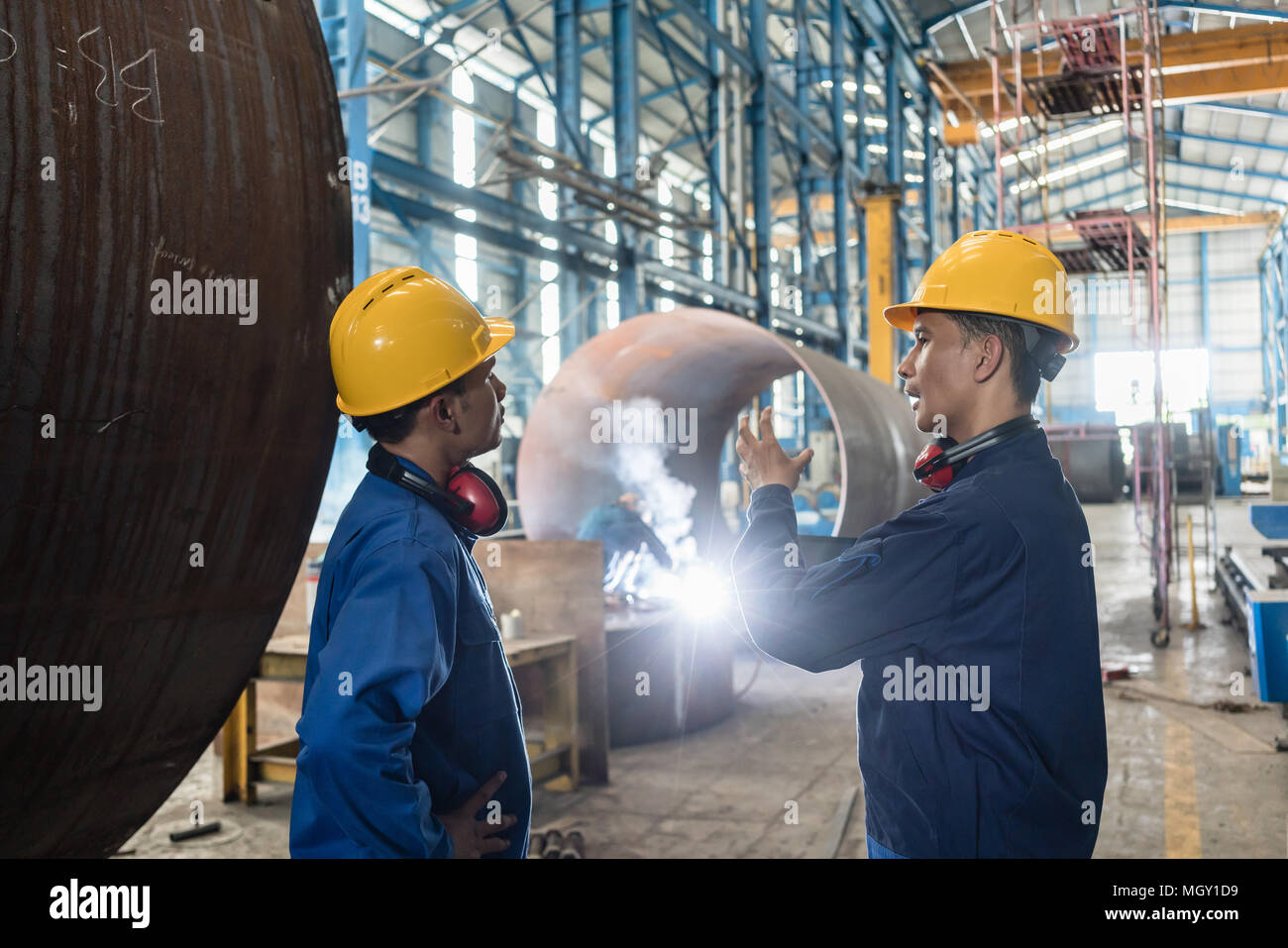 Two Asian experts talking while supervising fabrication - Stock Image