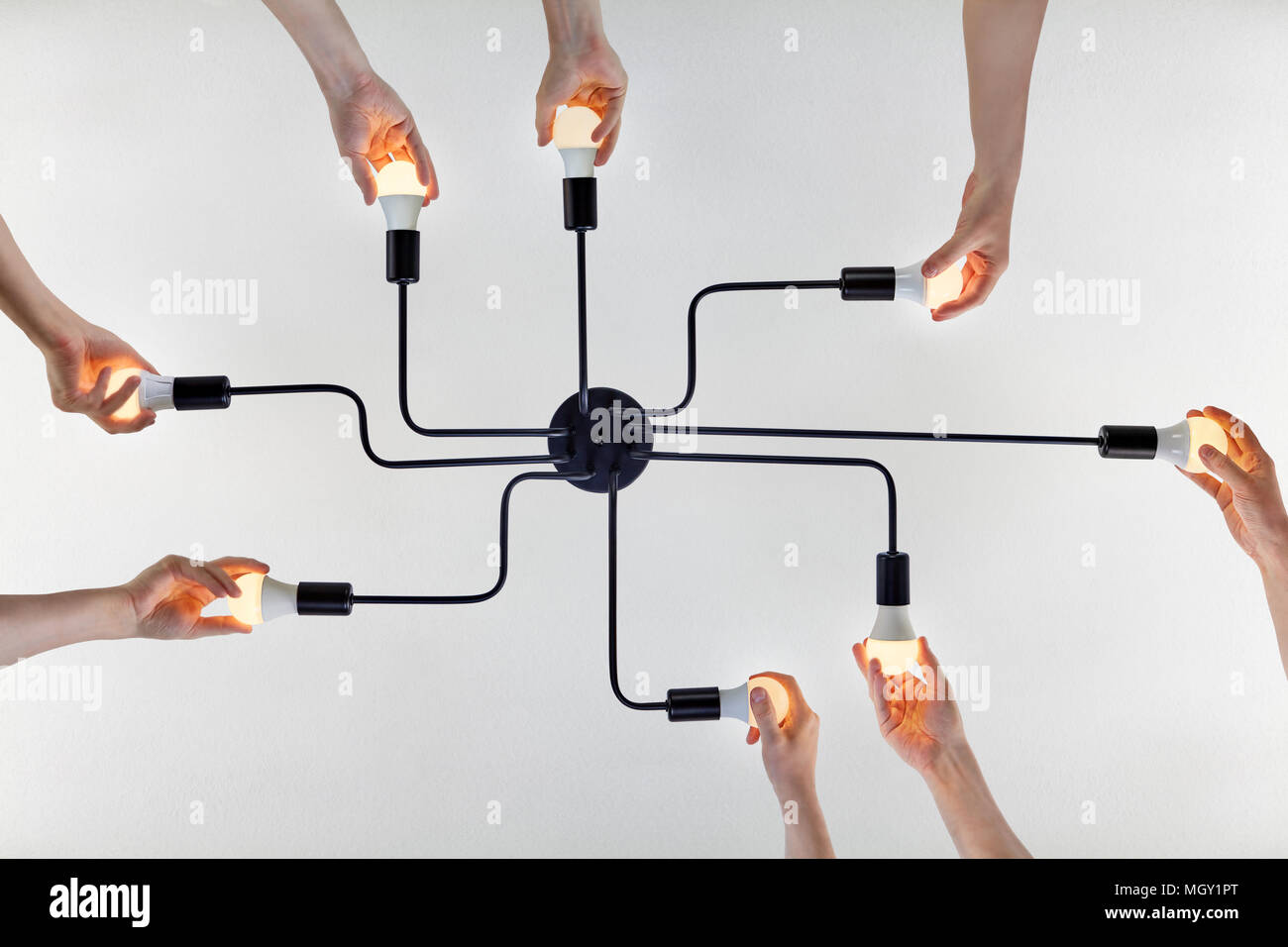 Concept of teamwork, or shared purpose on example of united actions when replacing LED lamps in a ceiling lighting. - Stock Image