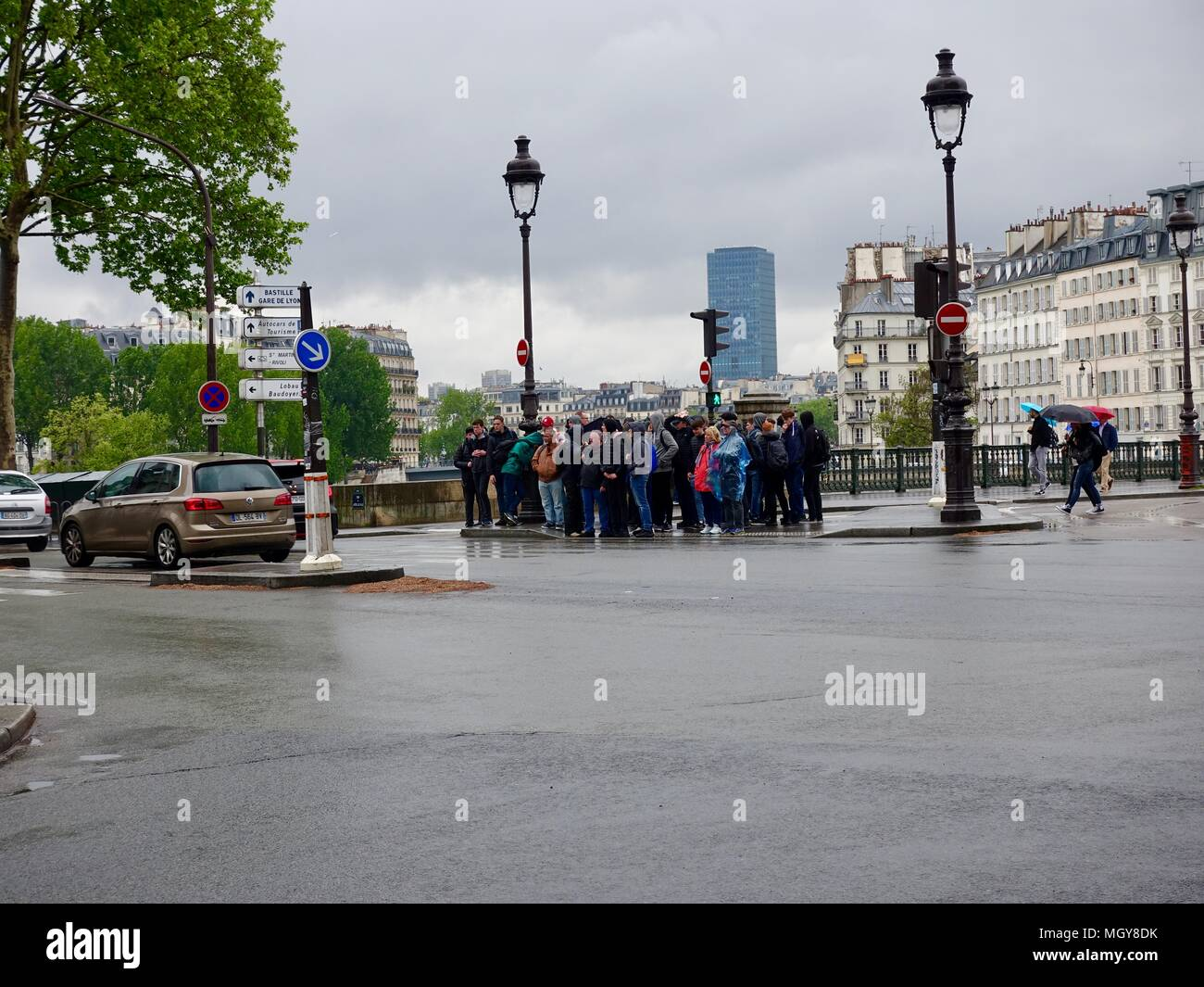 A crowd of tourists wait in the rain to cross the road in front of the Hôtel de Ville, Paris, France. - Stock Image
