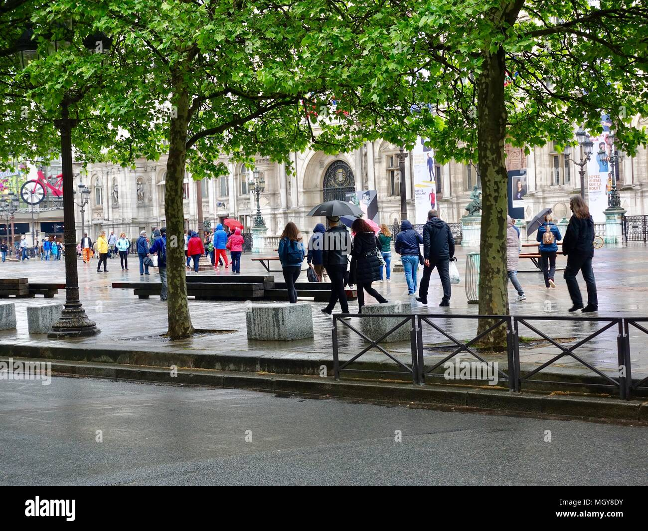 A crowd of tourists, wearing rain jackets and carrying umbrellas, walk in the rain across the plaza in front of the Hôtel de Ville, Paris, France. - Stock Image