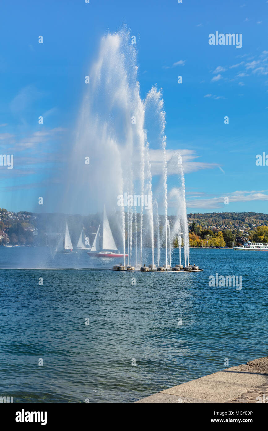 A fountain and boats on Lake Zurich in Switzerland. The picture was taken from the city of Zurich at the beginning of October. - Stock Image