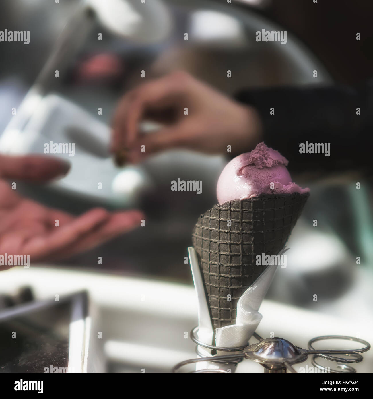Stand for ice cream. Delicious fresh ice cream in black cone. Cash payment. Real scene in the store, Purchase - Stock Image