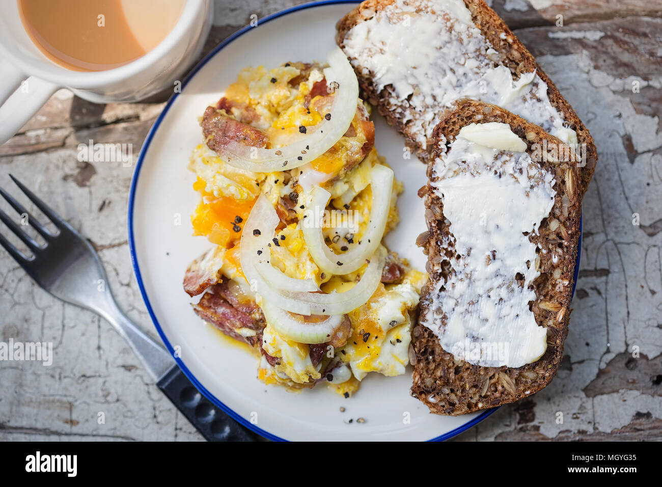 Scrambled eggs with bacon, sausage and onion with wholegrain bread and coffee - Stock Image