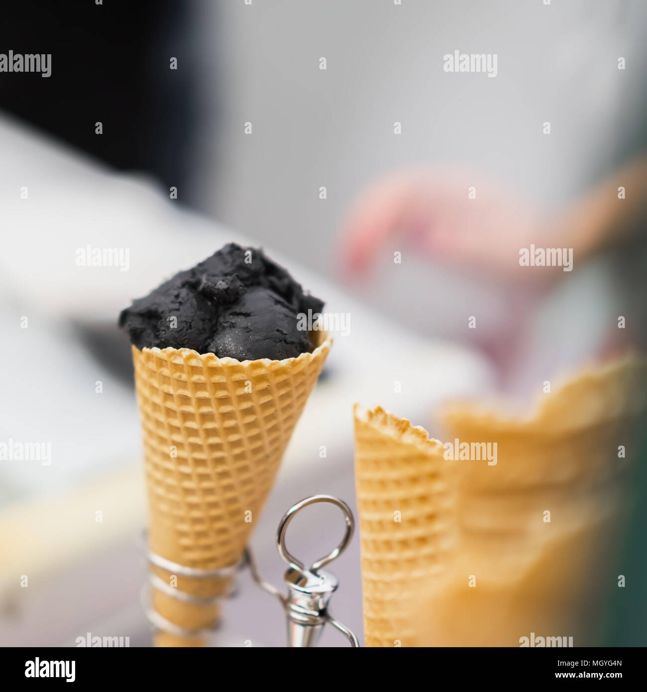Close-up of waffle cone with ball of trendy black ice cream. Delicious cooling portion on a hot day and just for fun. Selective focus. Real scene in s - Stock Image
