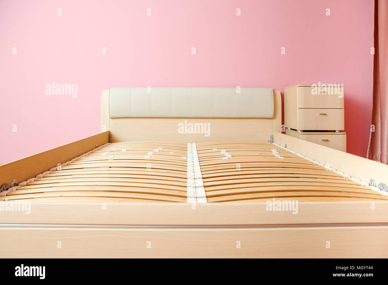Photo of bed without mattress, chest of drawers - Stock Image
