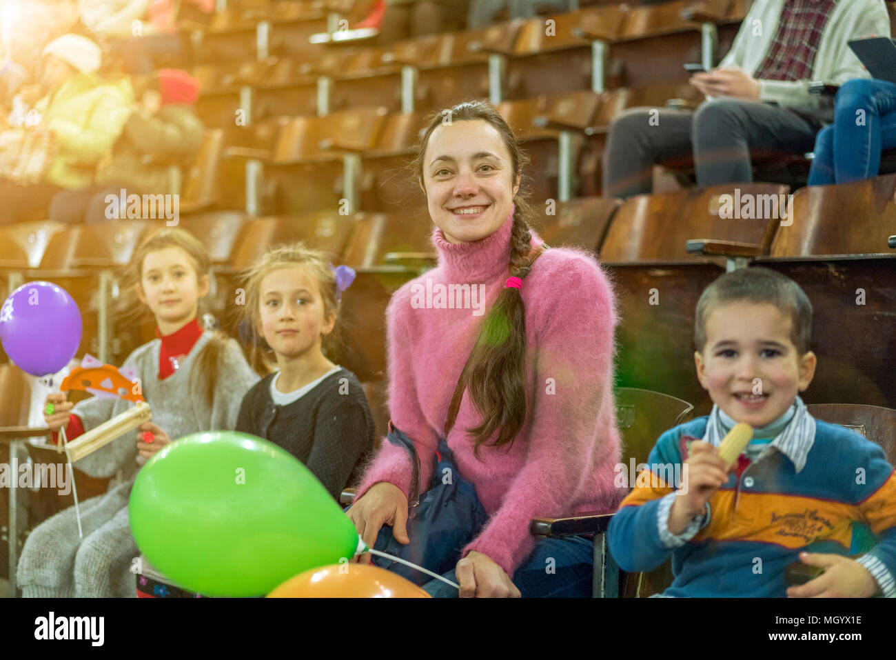 A mother with three children is sitting at a concert. Children with inflatable balls in the circus. Two sisters and a brother on the podium in the circus. - Stock Image