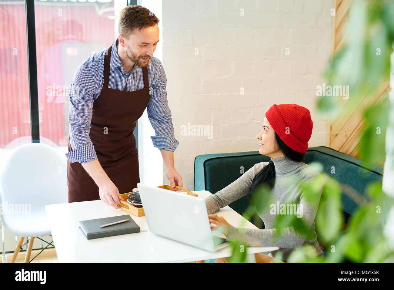 Waiter Serving Young Woman in Cafe - Stock Image