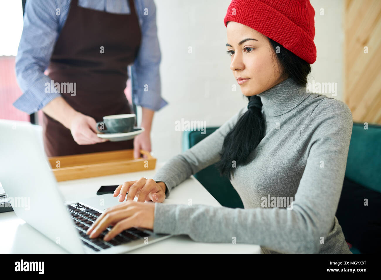 Modern Young Woman Using laptop in Cafe - Stock Image