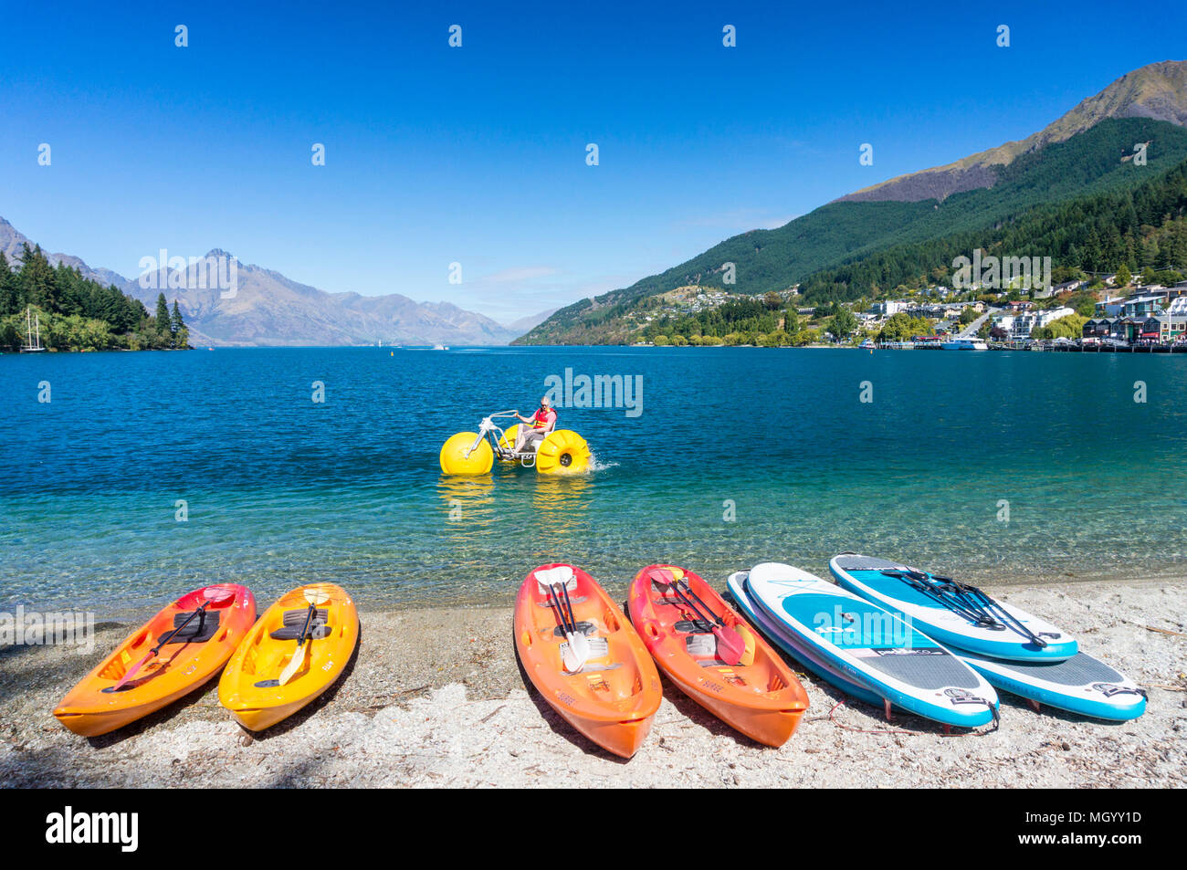 lake wakatipu from the lakeside with kayaks and water bicycles for hire and for rent rental kayaks lakeside queenstown South Island New Zealand - Stock Image