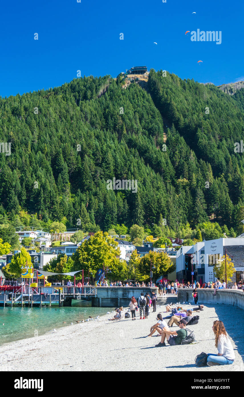 view of the queenstown skyline gondola queenstown hill from the sandy beach on lake wakatipu shore lakeside queenstown South Island New Zealand nz - Stock Image