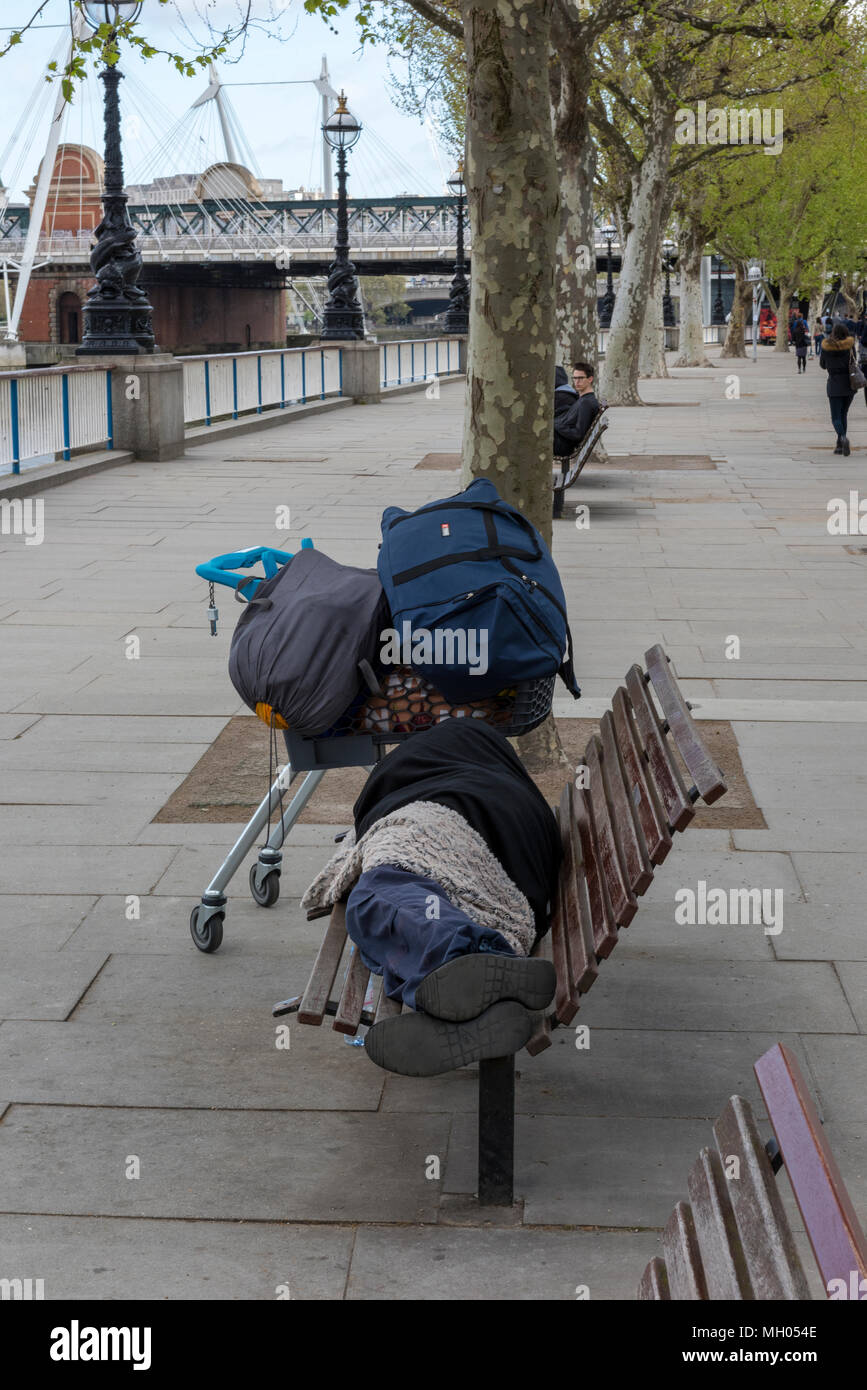 a vagrant or tramp on a bench sleeping rough in central London. Homelessness in the UK with belongings on a shopping trolley. Social problems in UK. - Stock Image