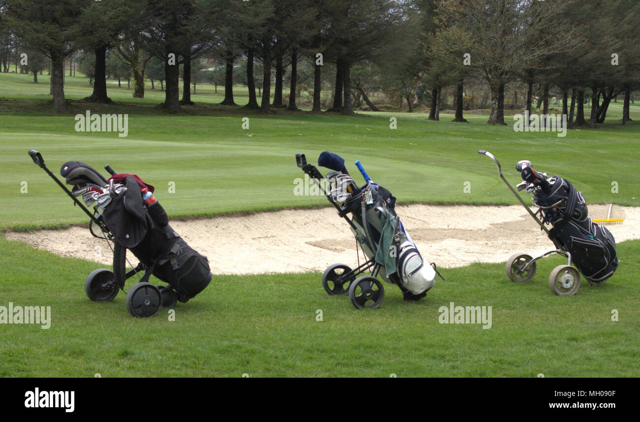 3 golf bags left in a line beside a sand bunker on the fairway of a golf course. - Stock Image