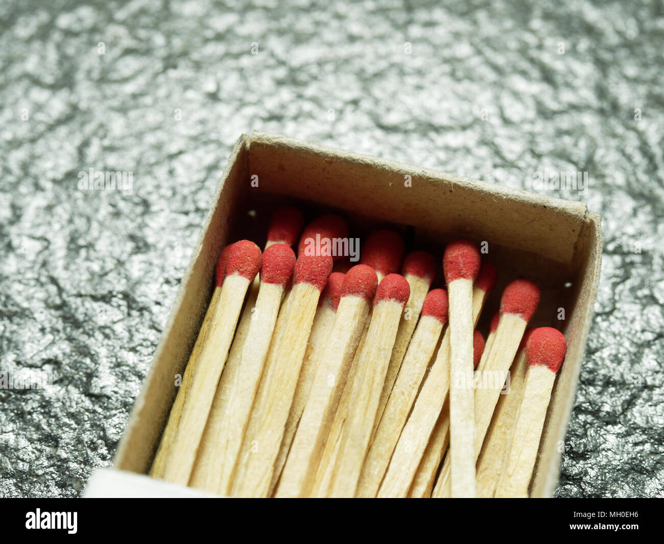 A group of wooden match sticks with red head in match box over black or dark granite texture with concepts of energy, old fashion, vintage, and retro - Stock Image
