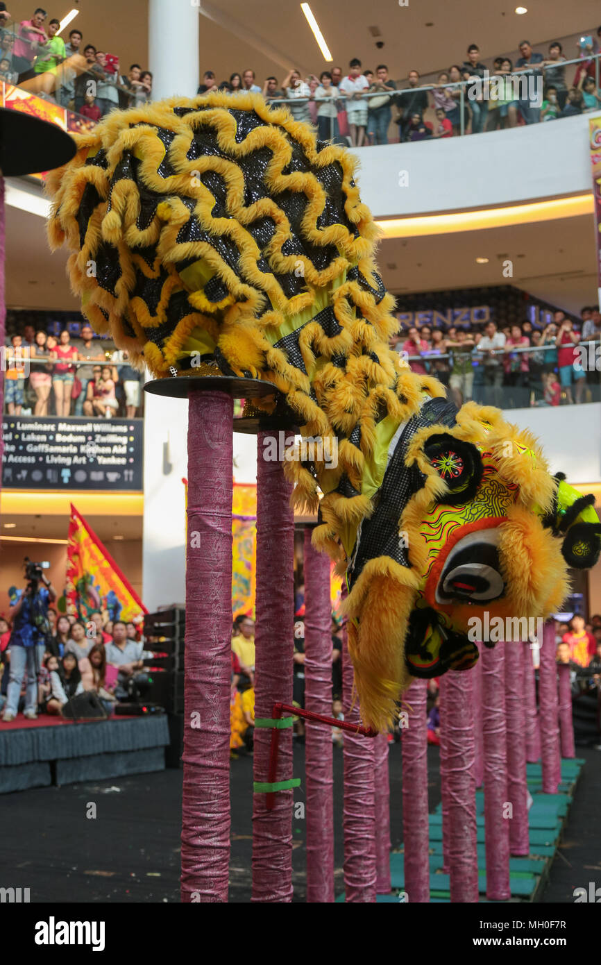 Yellow color lion dance grabing the prize on high poles at VIVA HOME shopping mall in Kuala Lumpur, Malaysia. Stock Photo