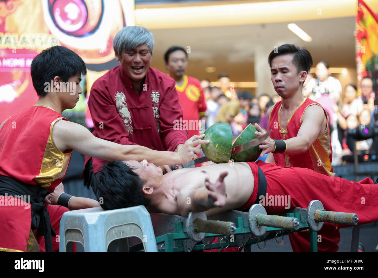Chinese traditional stuntman master using sword to cut watermelon laying on apprentice's tomach at VIVA HOME shopping mall in Kuala Lumpur, Malaysia. - Stock Image