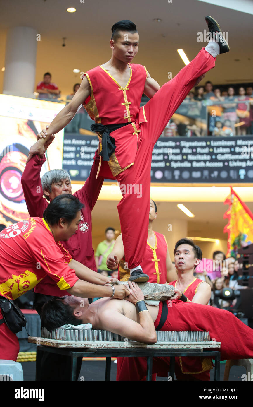 Chinese traditional stuntman stand on his coleague lying on needle bed at VIVA HOME shopping mall in Kuala Lumpur, Malaysia. - Stock Image