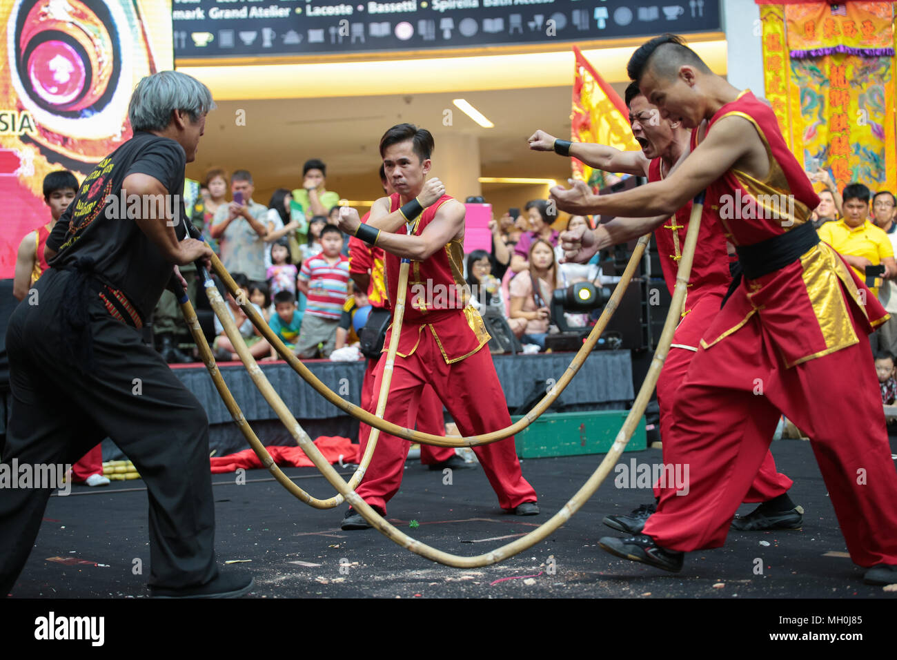 Chinese traditional stuntman bending bamboo spear with their throats at VIVA HOME shopping mall in Kuala Lumpur, Malaysia. - Stock Image