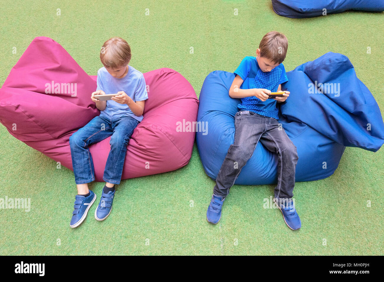 Children using mobile phone sitting on bag chairs - Stock Image