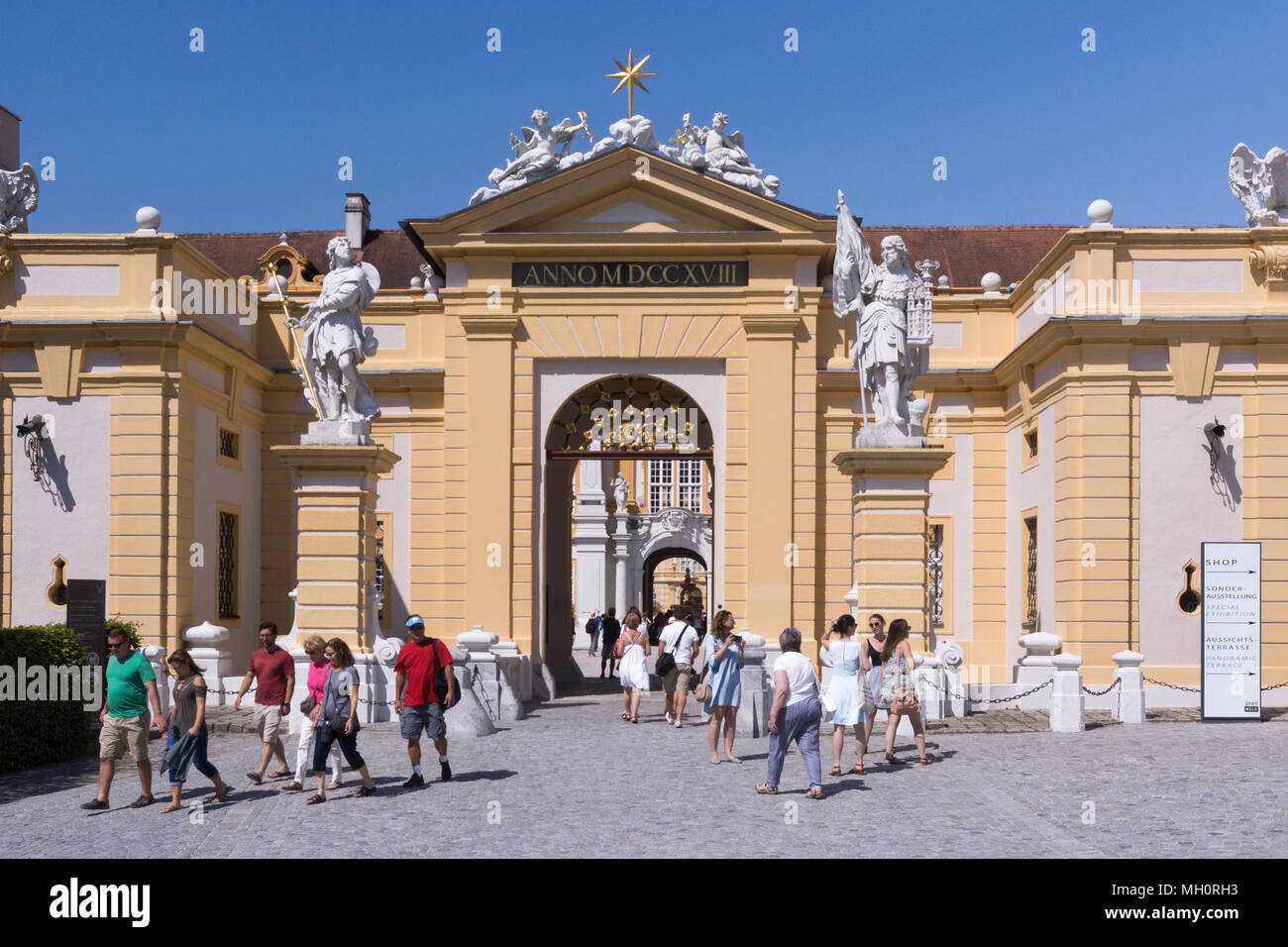 Visitors to Austria's Melk Abbey passing through the main gate. Its architecture is famous worldwide and part of UNESCO's world cultural heritage - Stock Image
