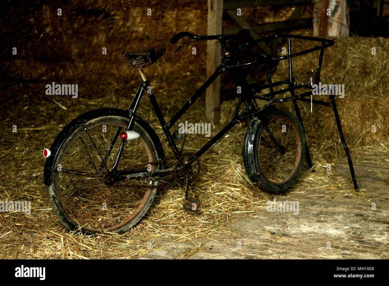 Period props from bygone era - vintage bicycle standing in hay barn. - Stock Image