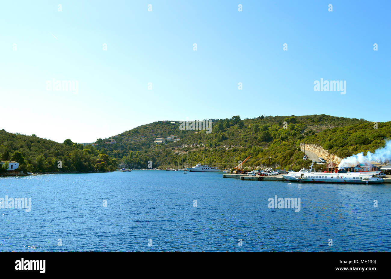 Tourist cruise ships in Antipaxos harbour ready to sail to Corfu - Stock Image