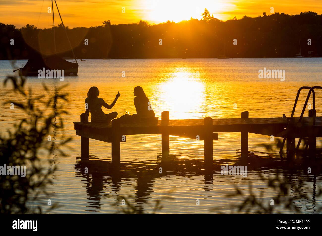 Zwei Frauen am See geniessen den Sonnenuntergang - Stock Image