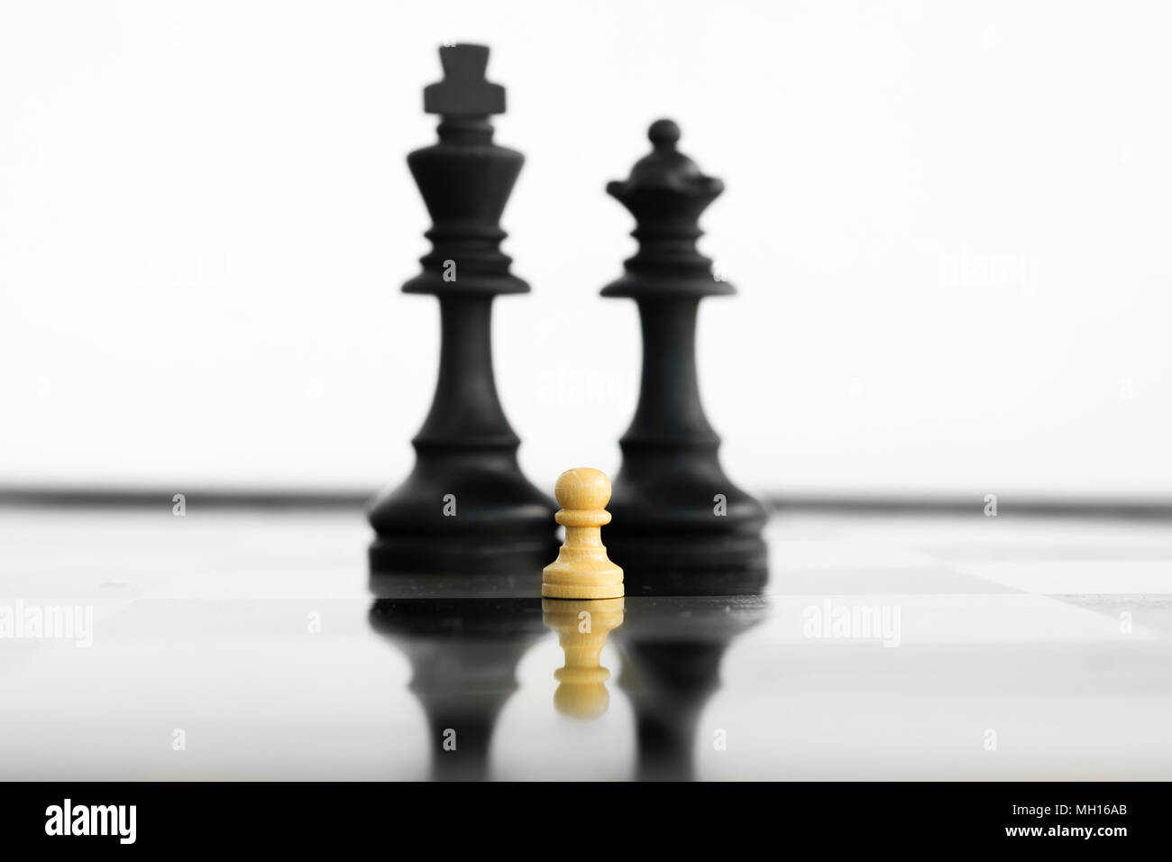 White peon standing in front of a defeated king and queen black chess army before confrontation
