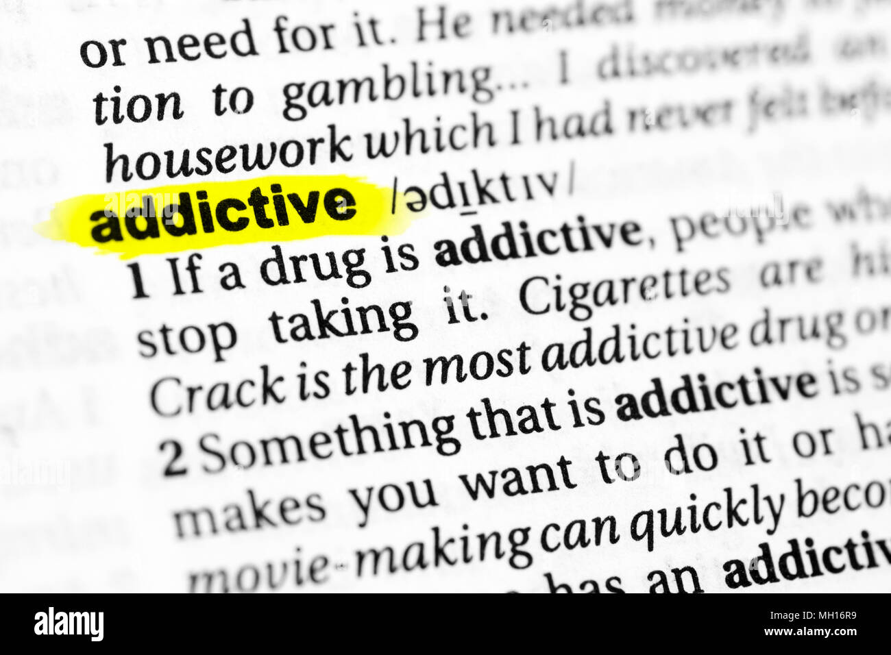 Highlighted English word 'addictive' and its definition in the dictionary. - Stock Image