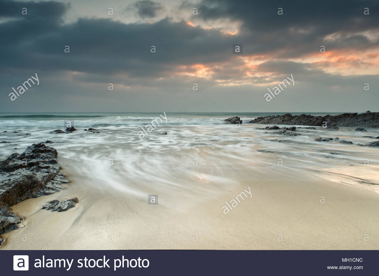 Outgoing tide on Gunwalloe Church Cove beach with a cloudy sunset - Stock Image