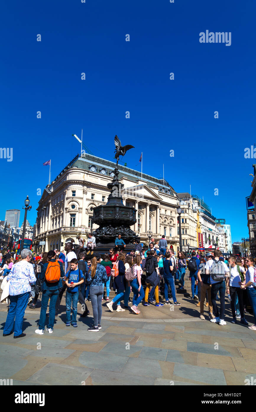 Busy square - Tourists walking in Piccadilly Circus and sitting on the steps of Shaftesbury Memorial Fountain, London, UK - Stock Image