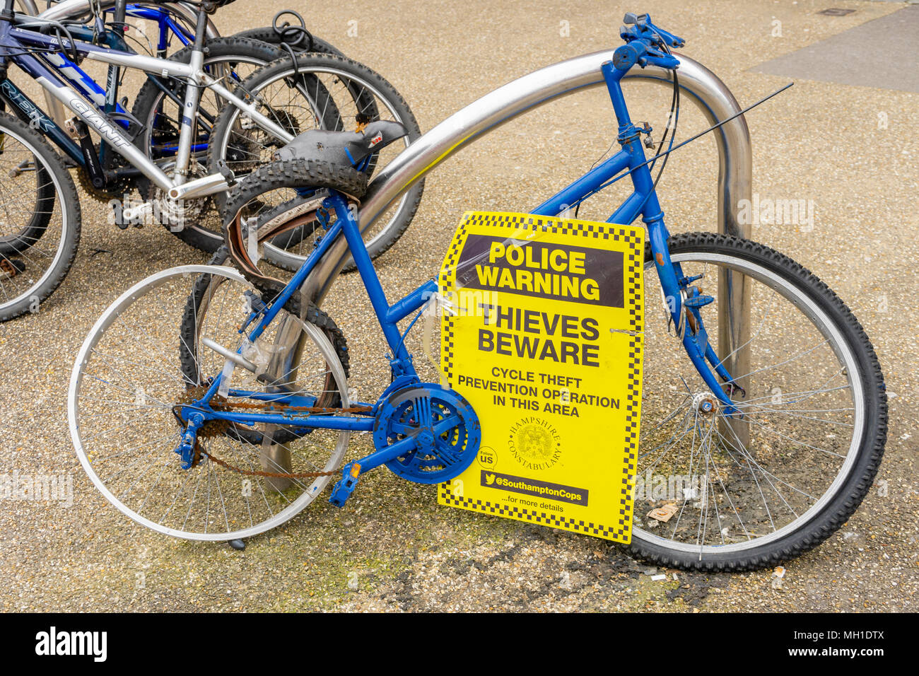 Blue dishevelled Bike on display in a street by Hampshire Constabulary with a police warning sign attached 'Thieves Beware' - Stock Image