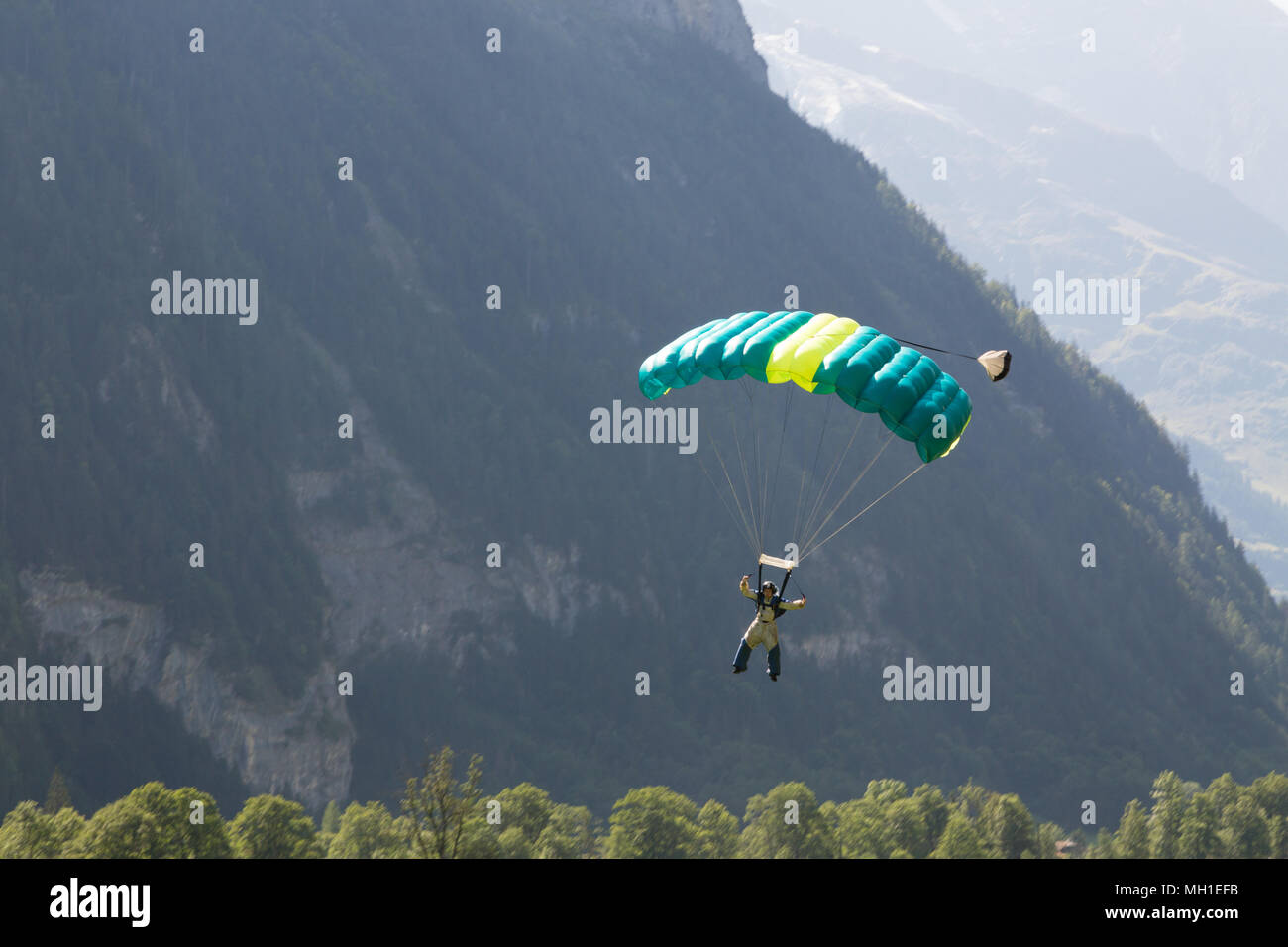Basejumper soaring with parachute open in Lauterbrunnen Switzerland - Stock Image