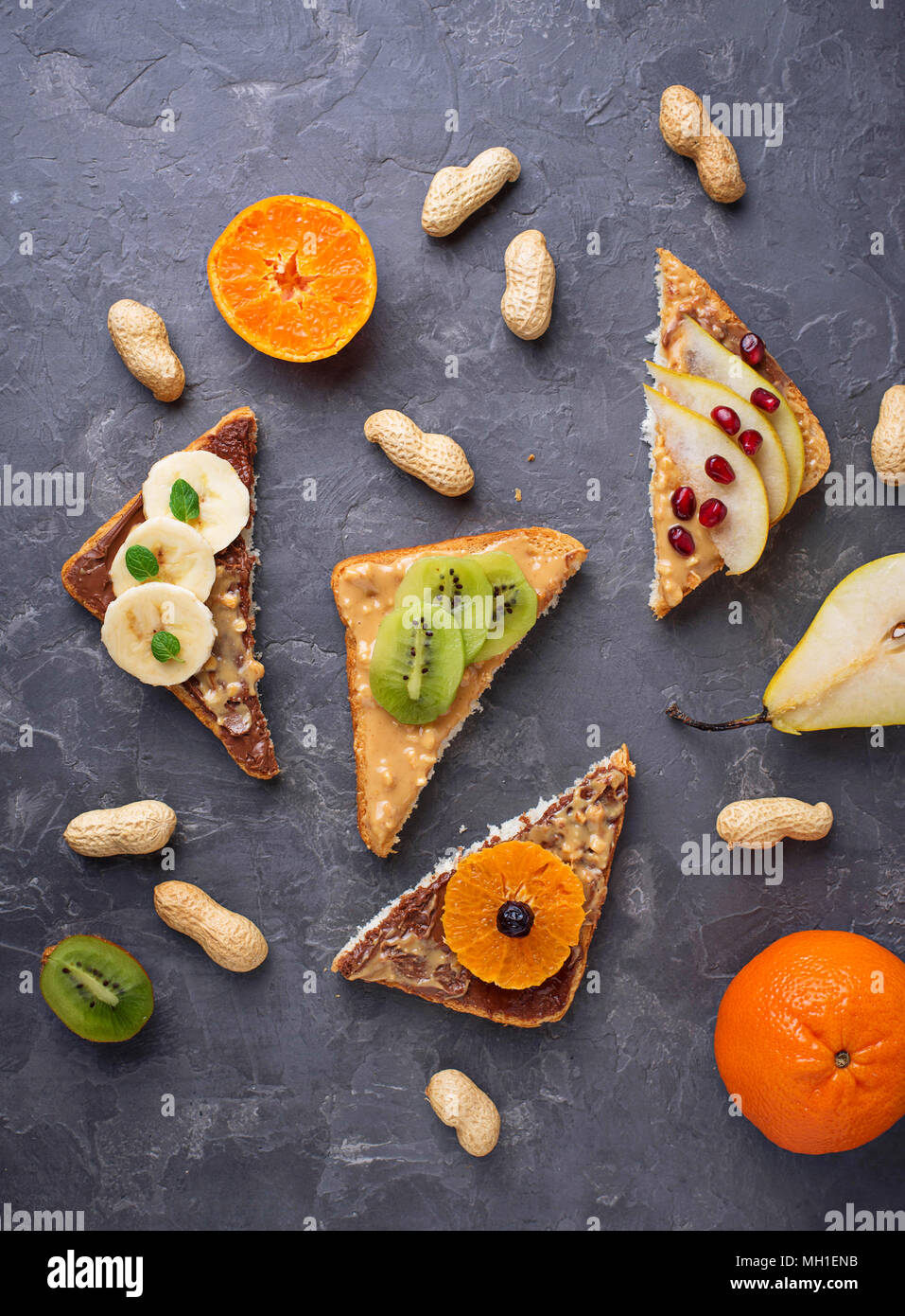 Healthy sweet sandwiches with peanut butter and fruits. Top view - Stock Image