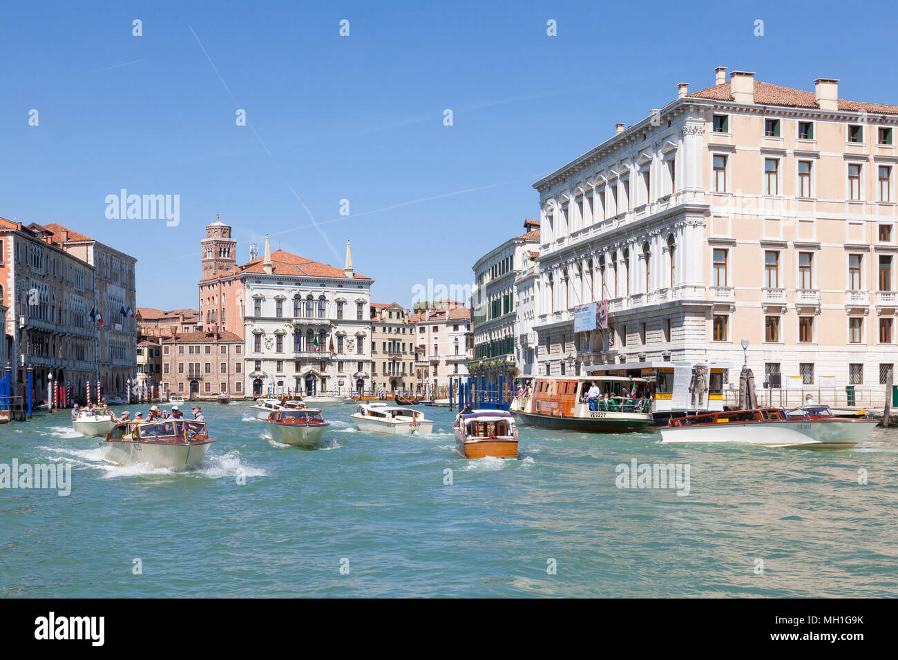 Very busy water taxi boat traffic  filled with tourists sightseeing on the Grand Canal,  San Polo, Venice, Veneto, Italy. The wakes of these boats are - Stock Image