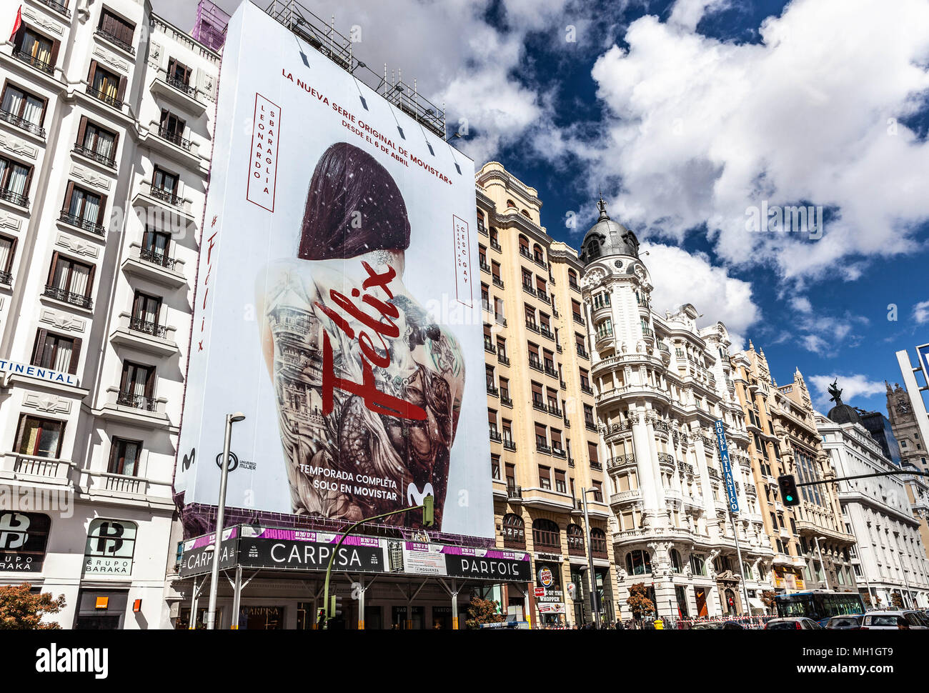 Giant vertical billboard covering building scaffolding, Gran Via, Madrid, Spain. - Stock Image