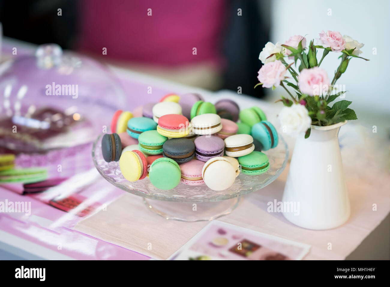 Different colorful macarons spring flowers roses tender pink different colorful macarons spring flowers roses tender pink background romantic morning gift present for beloved light backdrop negle Choice Image