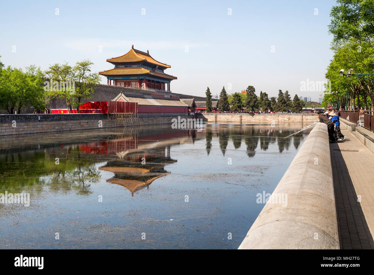 A group of friends catching fish in the moat surrounding the Forbidden City, Beijing, China. In the distance the Northern gate and crowds of tourists. Stock Photo