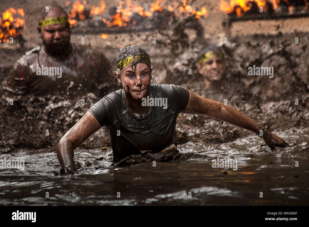 Contestants performing an extreme challenging assault course. - Stock Image