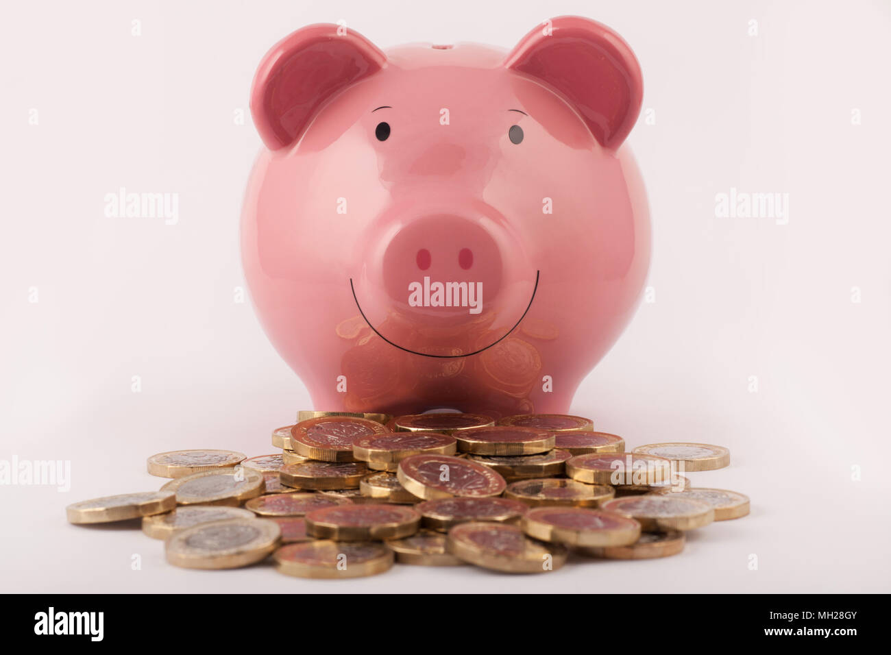 Piggy band and a pile of new (post 2016) pound coins - Stock Image