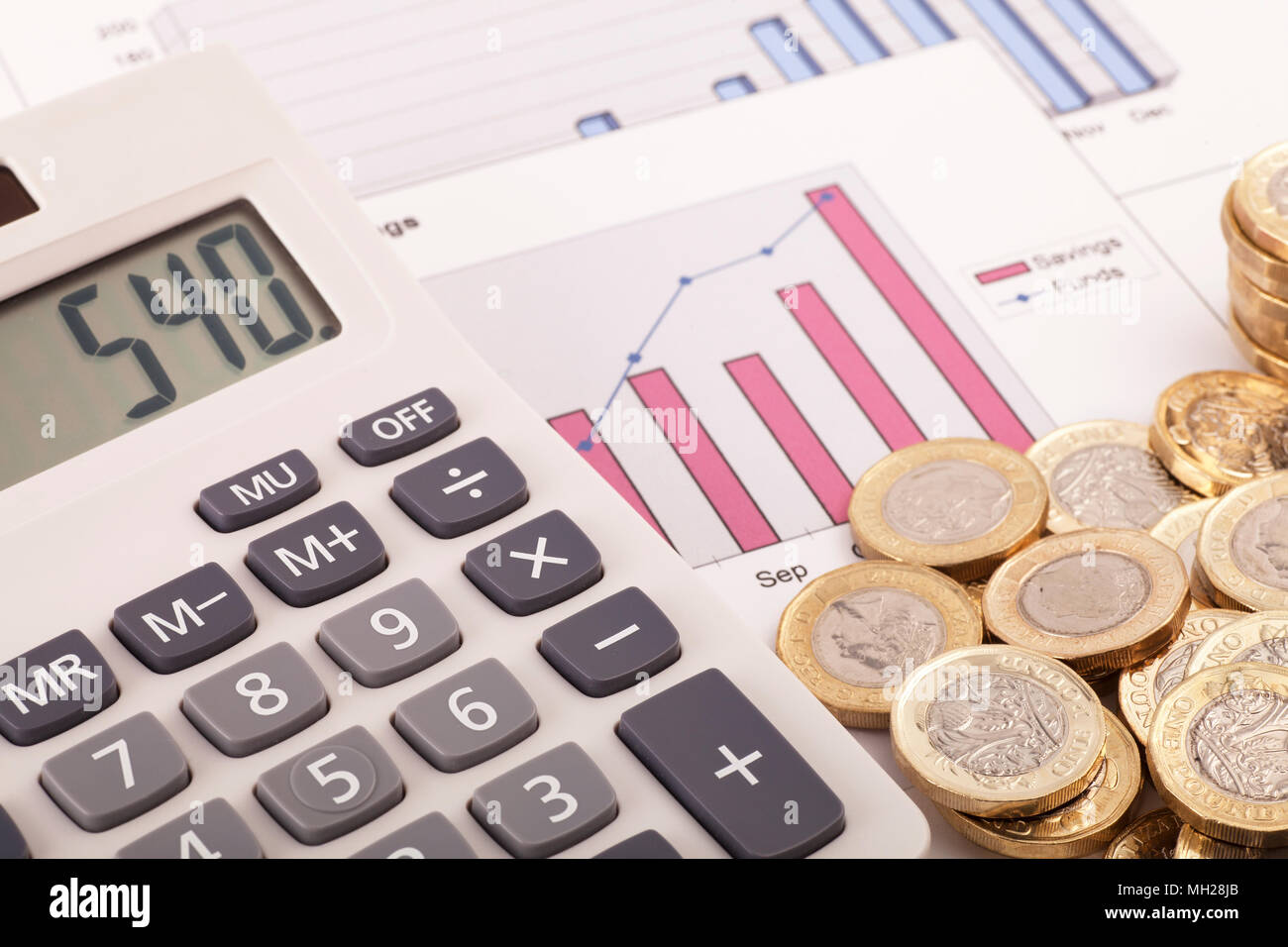 A calculator sitting on some graphs labelled savings and funds with some new (post 2016) pound coins. - Stock Image