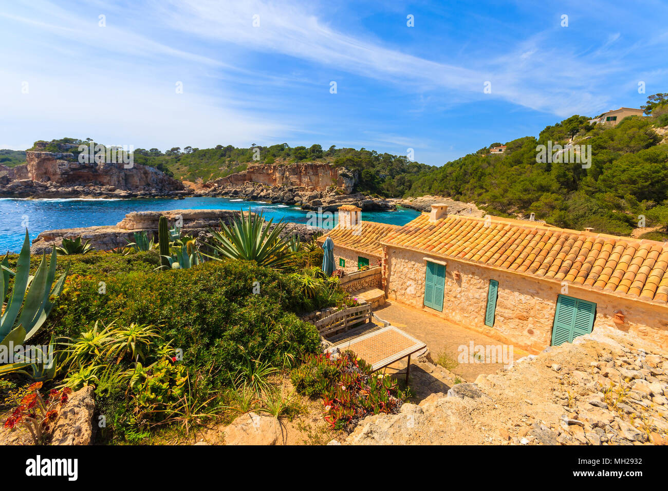 Typical stone house in beautiful bay with beach, Cala S'Almunia, Majorca island, Spain - Stock Image