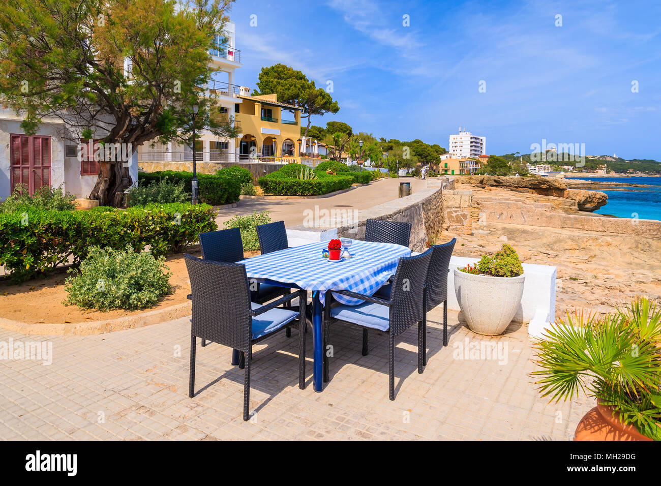 Restaurant table on seashore in small village near Cala Ratjada, Majorca island, Spain - Stock Image