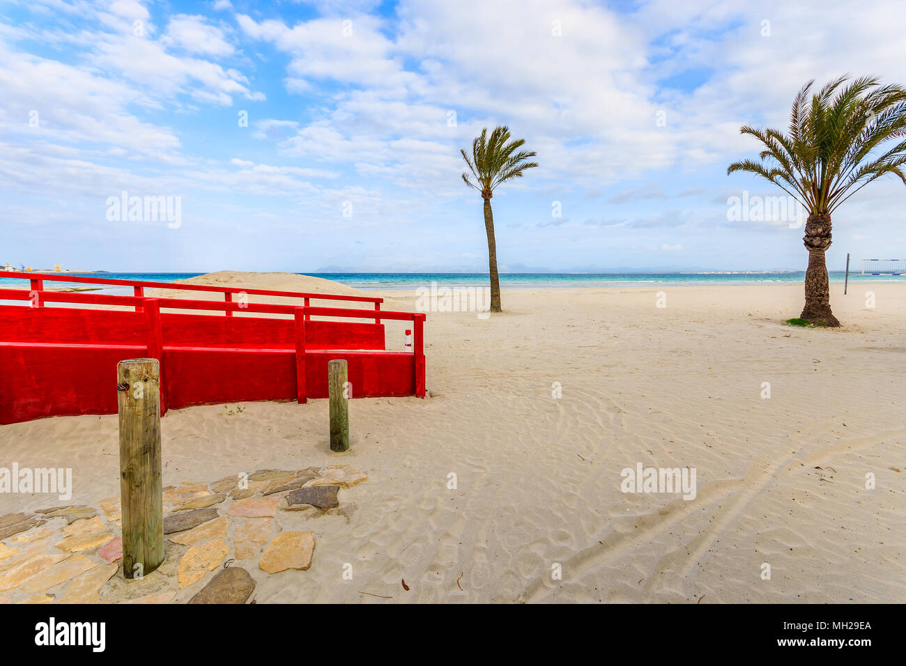 Red footbridge and palm trees on sandy Alcudia beach at early morning, Majorca island, Spain - Stock Image